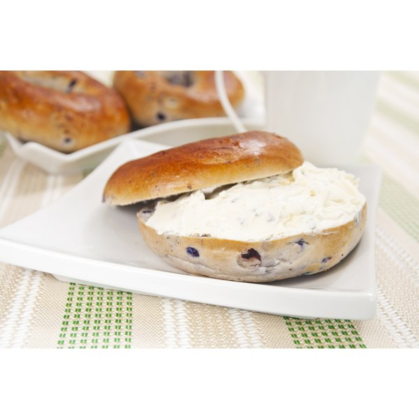 A blueberry bagel with cream cheese on a plate.