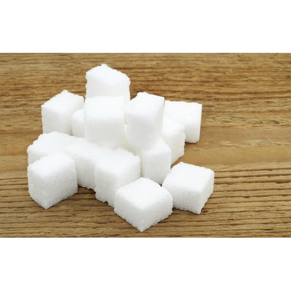 A pile of sugar cubes on a wood surface.