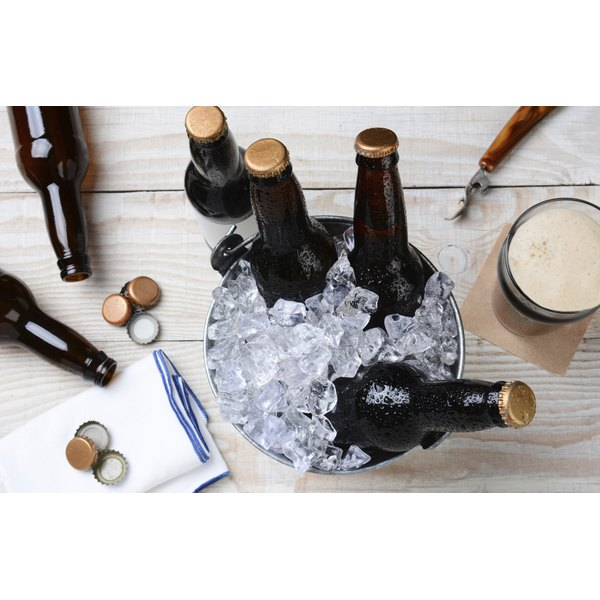 An overhead view of bottles of beer, an ice bucket, an opener and bottle caps.