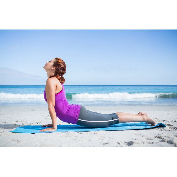 A woman is stretching on the beach.
