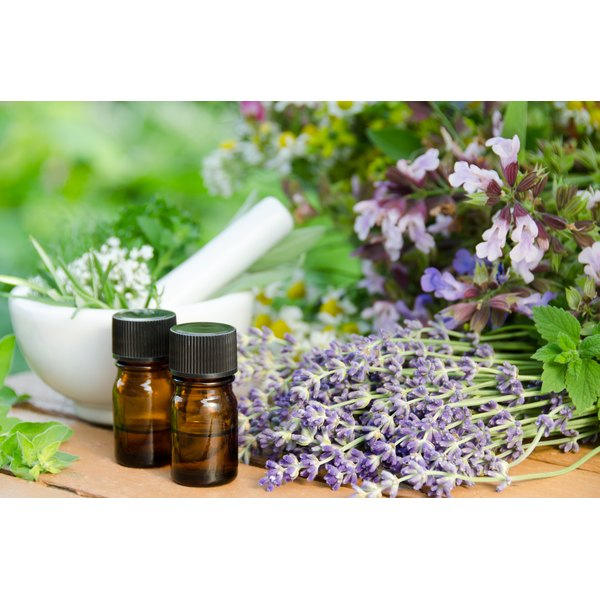 Bottles of essential oil on a garden table with a mortar and pestle and fresh herbs.