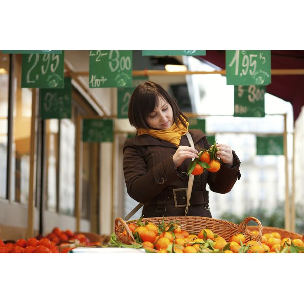 A woman picks tangerines in a marketplace.
