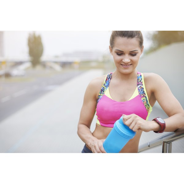 A woman about to go for a run opens a blue protein shake cup.