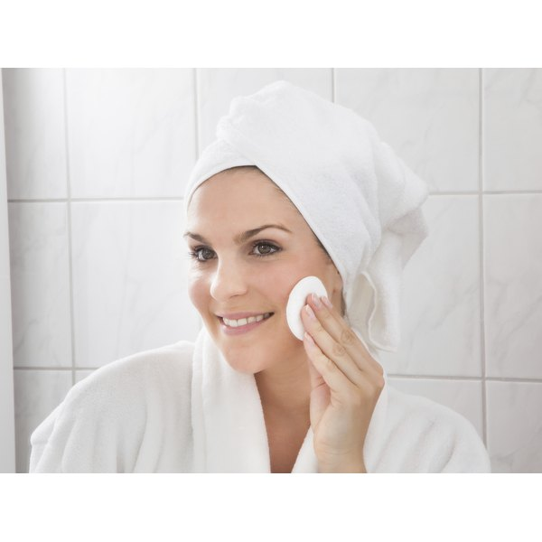 A woman applies anti-aging creme to her face in front of the mirror in the bathroom.