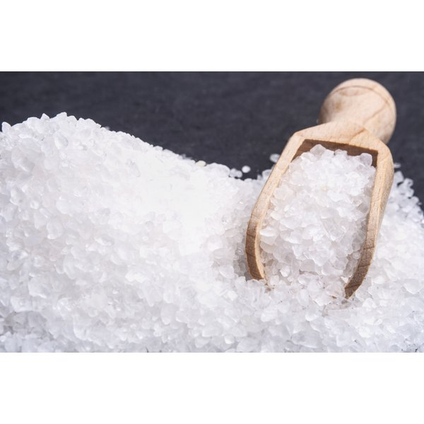 A wooden scoop sits in a pile of coarse sea salt.