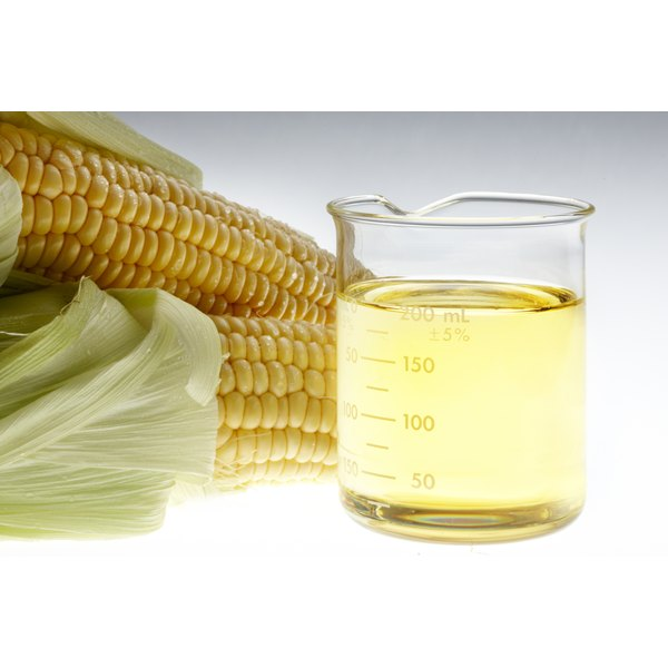 Corn on the cob next to a cup of corn oil.