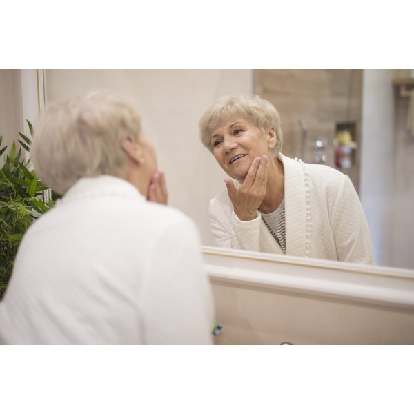 An older woman is looking in the mirror at her skin.