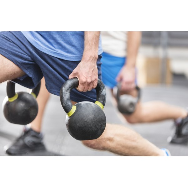 Two men lunging while holding kettlebells.