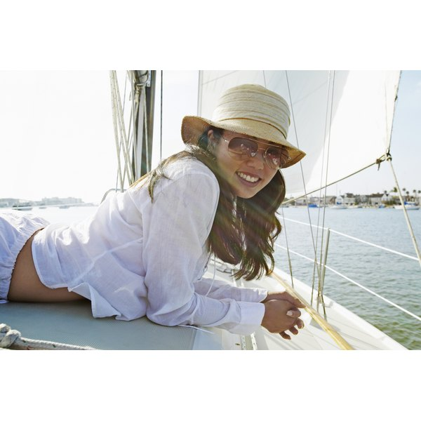 Woman wearing sunglasses and a hat on a boat