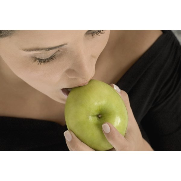 Woman biting into a green apple