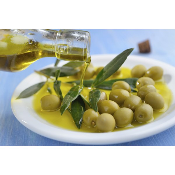 Olive oil being poured onto a plate with olives.