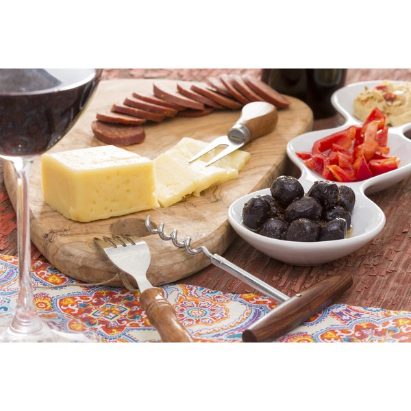 A block of havarti cheese on a cutting board next to crackers, olives and sliced red peppers.