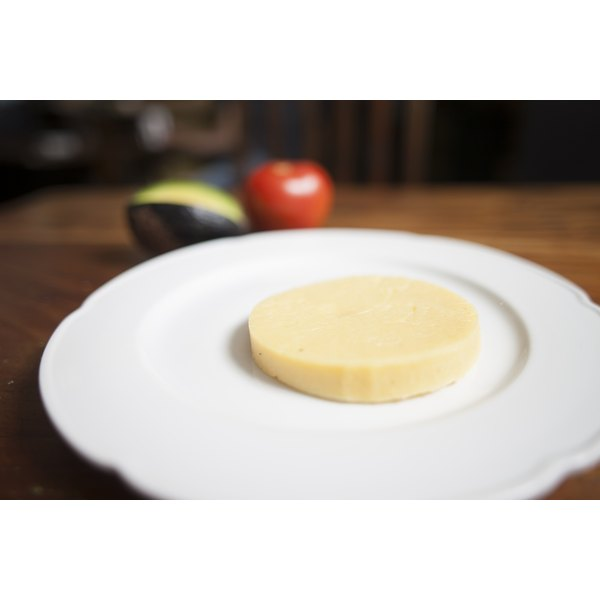 A slab of provolone cheese on a white plate.