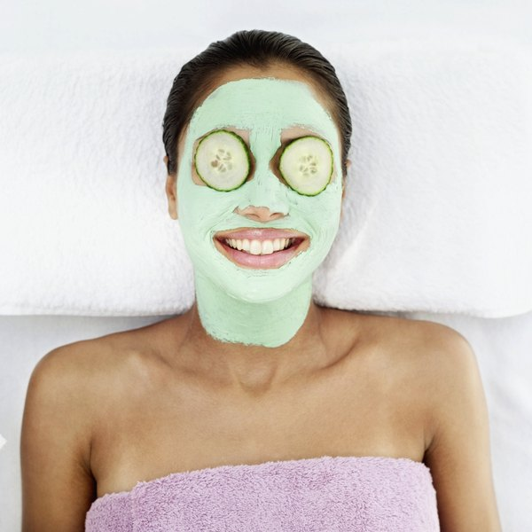 A young woman with a cucmber mask on her face and cucmber slices on her eyes, lies back at a spa.