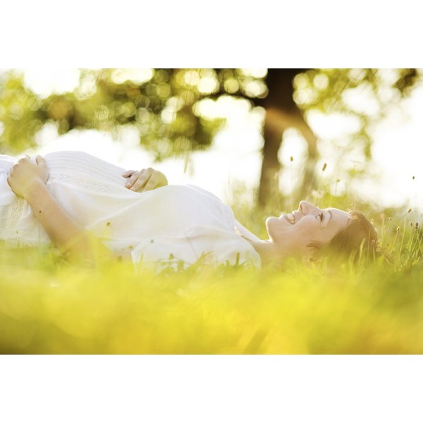 Pregnant woman laying down and smiling in grass.