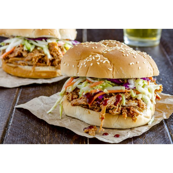 A pulled pork sandwich with coleslaw on a wooden table.