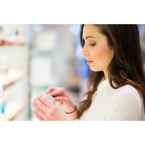 A woman is shopping for skin ointment or lotion in a cosmetics store.