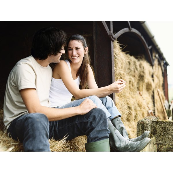 A happy couple sitting on bales of hay in a barn.