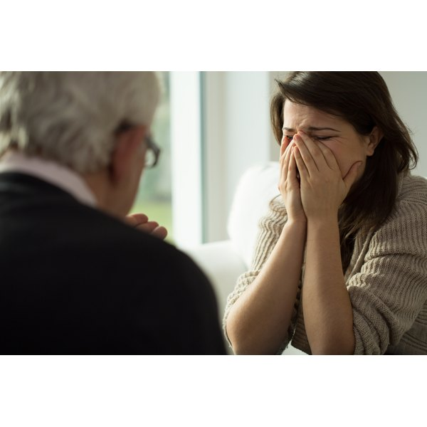 A woman crying while talking to her therapist.