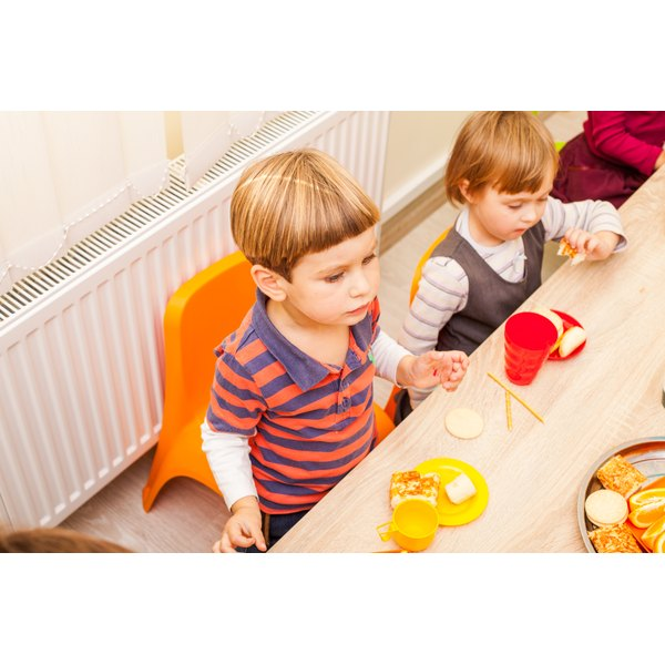 Two young children are eating at a lowered table.