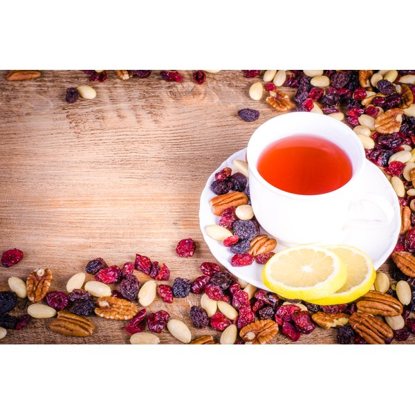 A cup of cranberry hibiscus tea sits on a wooden table surrounded by dried fruit and nuts.