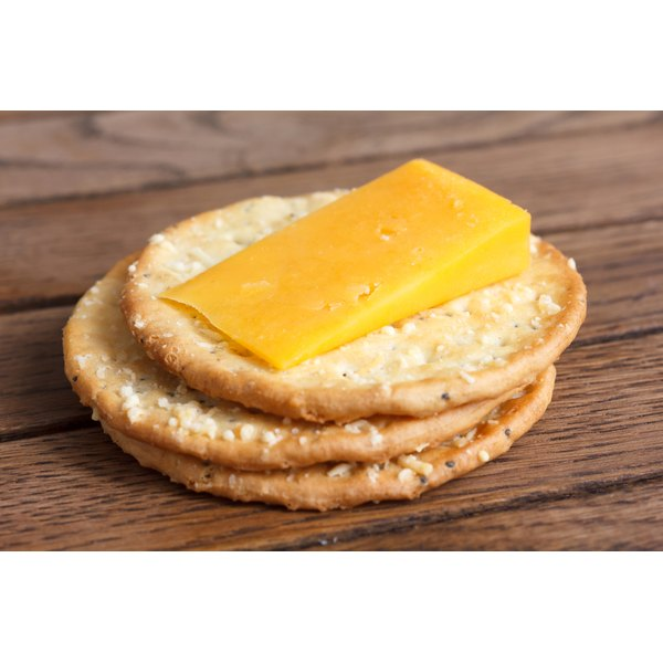 Sliced cheddar cheese on a whole grain cracker.