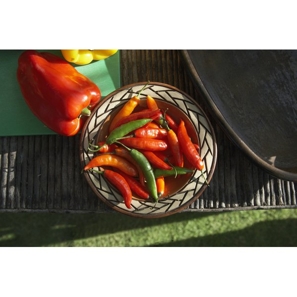 Bell and chile peppers on a sunny outdoor table.
