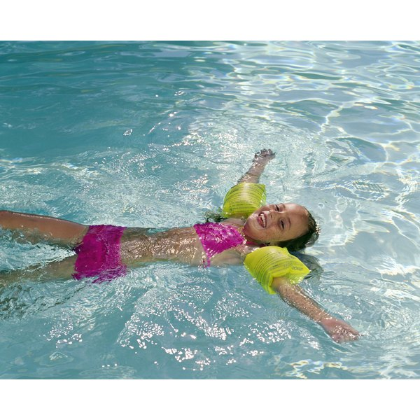 A young girl floats on her back in a pool with floaties on.
