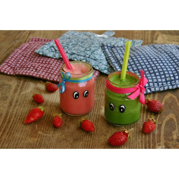 Jars of homemade juice for kids on a table with strawberries.