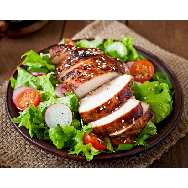 Grilled chicken breast served over a salad.