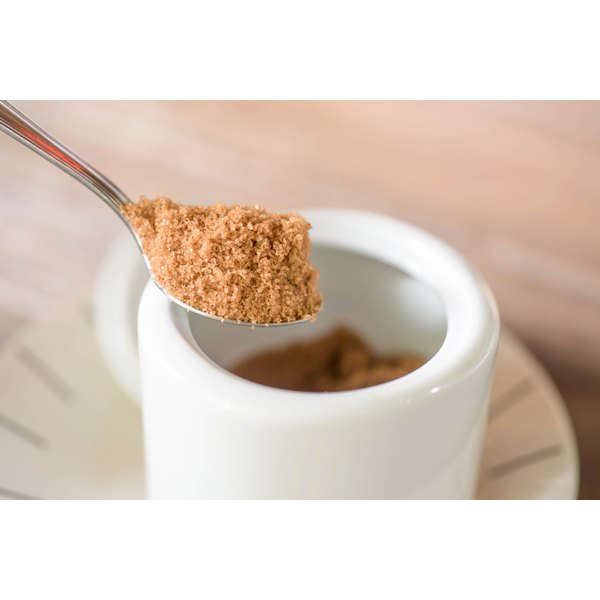 A spoonful of brown sugar from a sugar bowl.