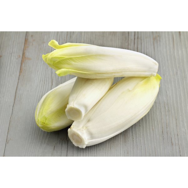 A small pile of endives on a wood surface.