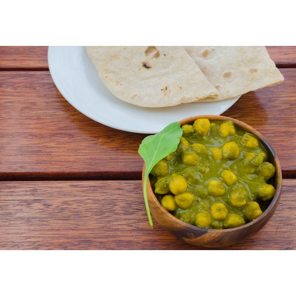 A bowl of curried chick peas garnished with a curry leaf.