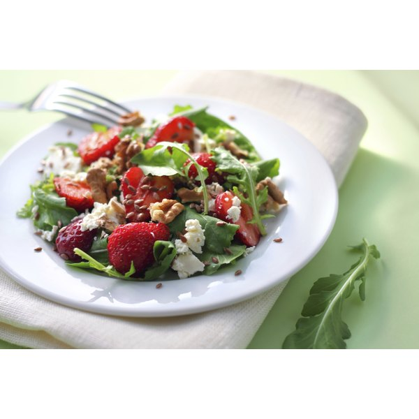 An arugula salad with strawberries, goat cheese, flax seeds, and walnuts.