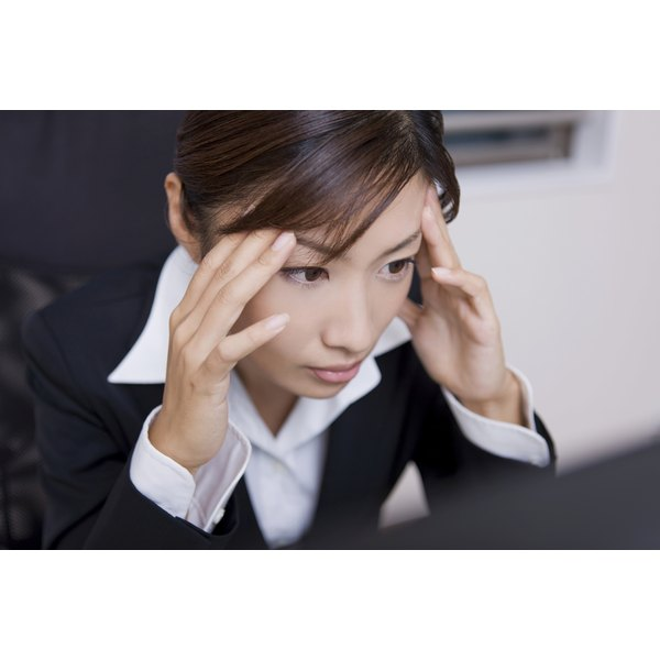 A woman with a headache at work.