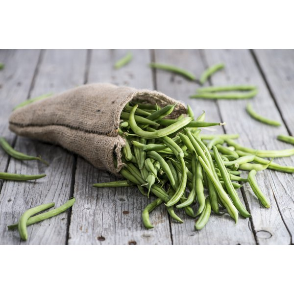 A small sack of green beans on a wood table.