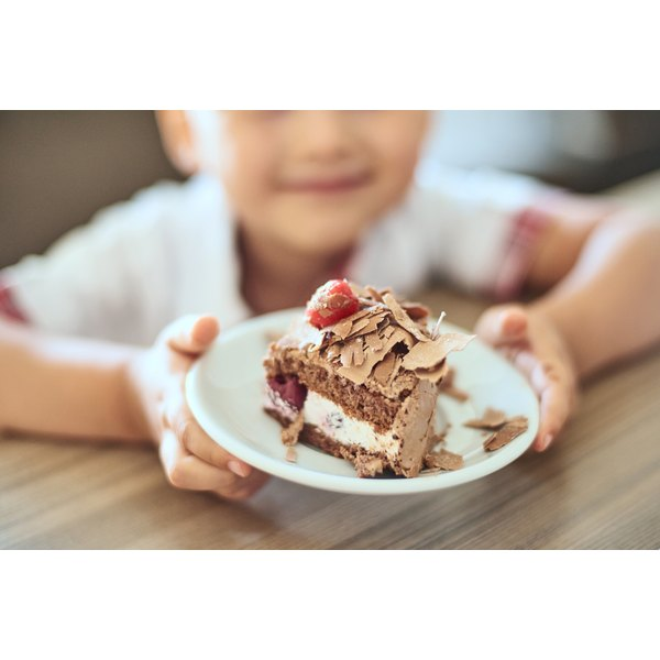 A child holds a plate with chocolate cake.