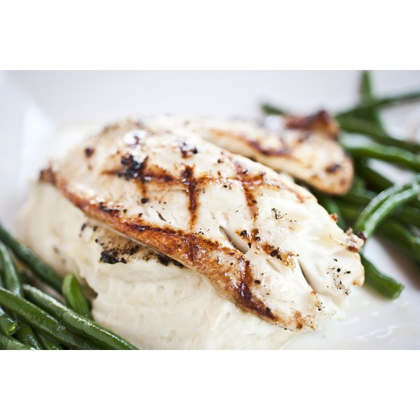 Grilled mahi mahi served on a bed of mashed potatoes with green beans on the side.