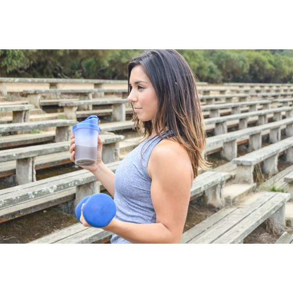 A woman is holding a protein shake.