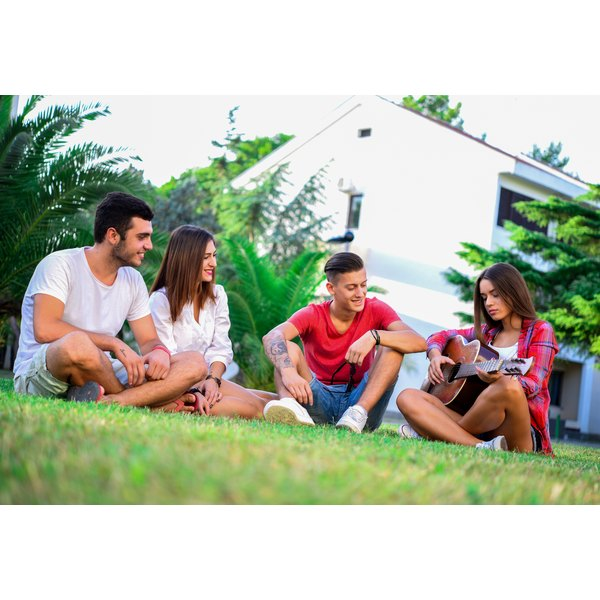 Friends socializing together sitting in circle in outdoor setting.