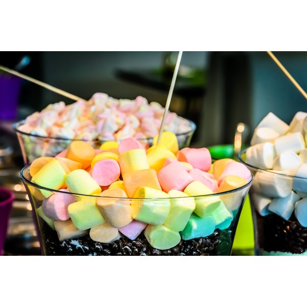Bowls of marshmallows and candies on a party table.