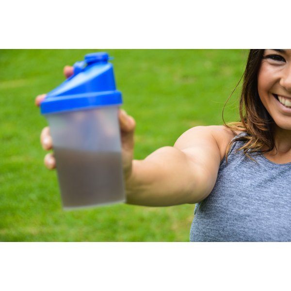 A woman is holding out a shaker bottle.