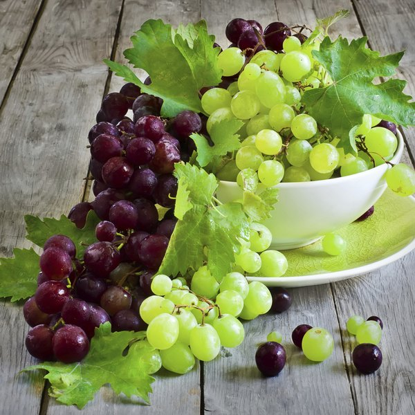 Red and green grapes in a bowl on a wood table.