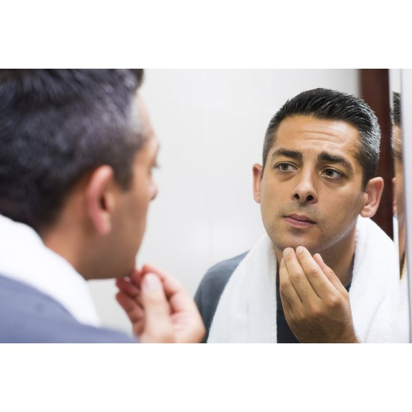 Man looking at his face in the mirror