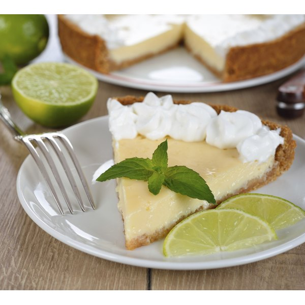 A slice of key lime pie with mint and lime garnish.