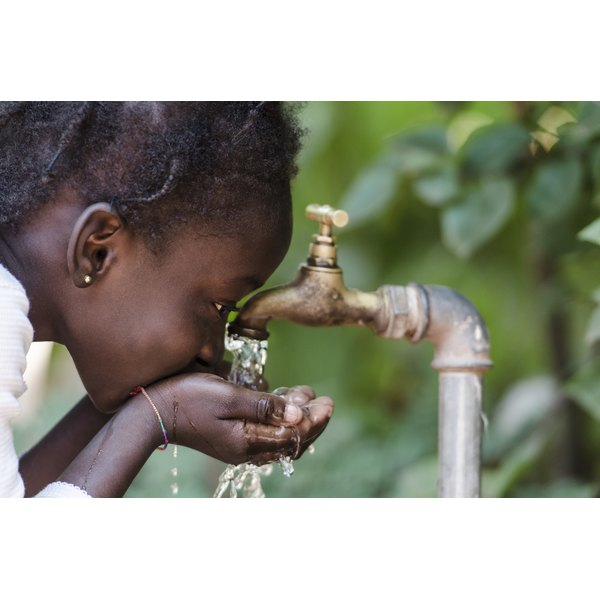A young African girl drinks water from a tap