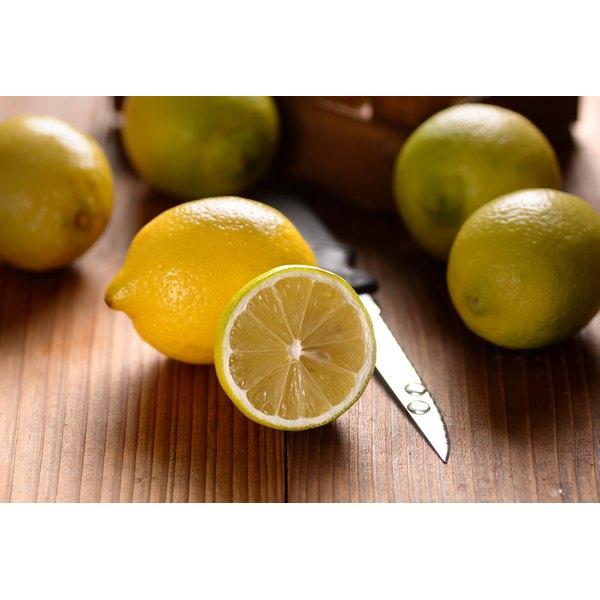 Whole and cut lemons next to a knife