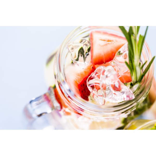 Flavored water with sprigs of mint and strawberries.