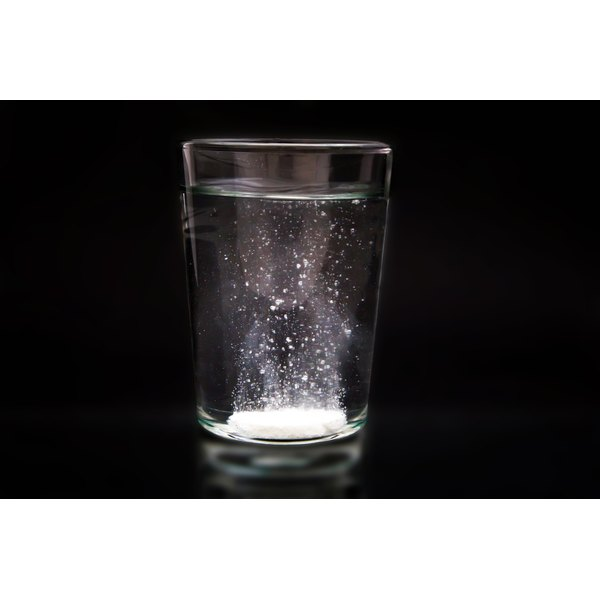 A soluble calcium supplement dissolves in a glass of water on a black background.
