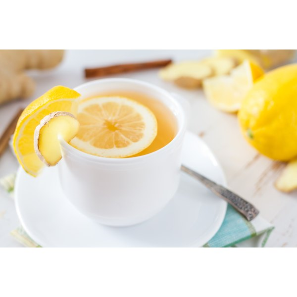 A cup of ginger tea with lemon slices.